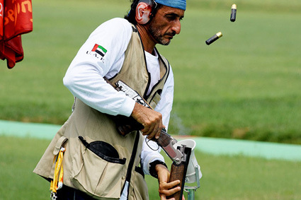 Emirati shooter Sheikh Ahmed bin Hasher al-Maktoum, a member of Dubai's ruling family, empties cartridges from his rifle during the men's trap shooting qualifications for the 2008 Beijing Olympics at the Shooting Range Hall in the Chinese capital on August 9, 2008. AFP PHOTO/ISSOUF SANOGO